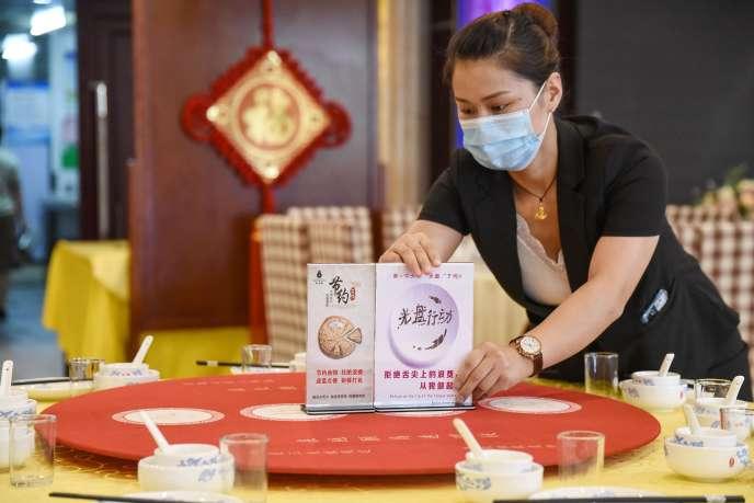 Une employée d'un restaurant à Handan, dans la province d'Hebei, le 13 août 2020, met en place l'opération «un plat en moins», en réaction à l'appel du dirigeant chinois Xi Jinping encourageant ses compatriotes à ne plus gaspiller de nourriture.