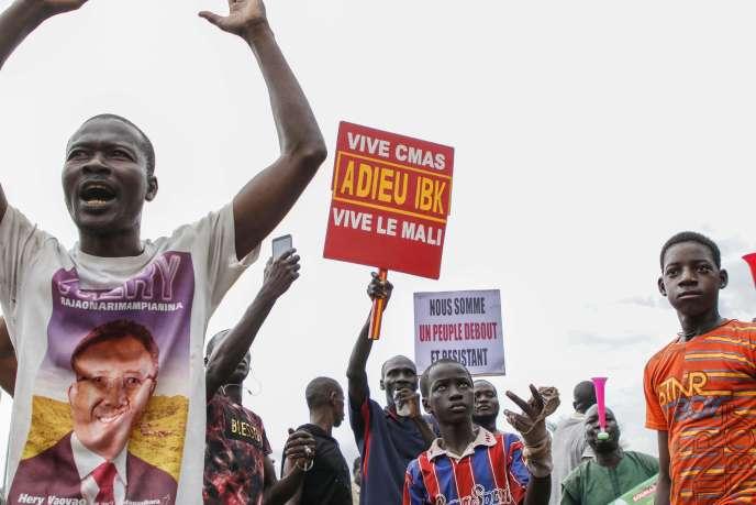 Des manifestants sur la place de l'Indépendance, à Bamako au Mali, mardi 18 août. On peut lire sur la pancarte« Adieu IBK», en référence au départ du président malien Ibrahim Boubacar Keïta, à la suite d'une prise de pouvoir de l'armée.