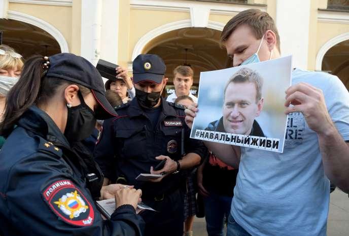 Des policiers contrôlent l'identité d'un participant à une manifestation de soutien à Alexeï Navalny,à Saint-Pétersbourg (Russie), le 20 août.