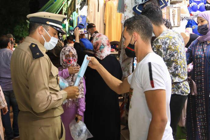 Un policier distribue des masques à Marrakech, le 17 août 2020, face à la flambée de la pandémie de Covid-19.