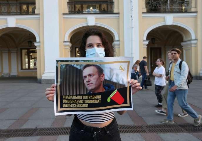 Sur une place de Saint-Pétersbourg, une femme tient une pancarte en faveur d'Alexeï Navalny, hospitalisé en Sibérie, le jeudi 20 août.