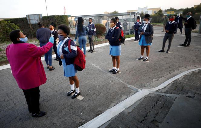 Une professeure contrôle la température des élèves dans le township de Langa, au Cap, en Afrique du Sud, le 8juin 2020.