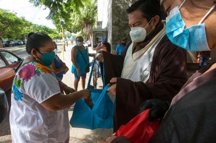 Des personnes distribuent de la nourriture aux parents de patients, à l'hôpital Ignacio-Garcia, à Mérida (Yucatan), le 15 août.