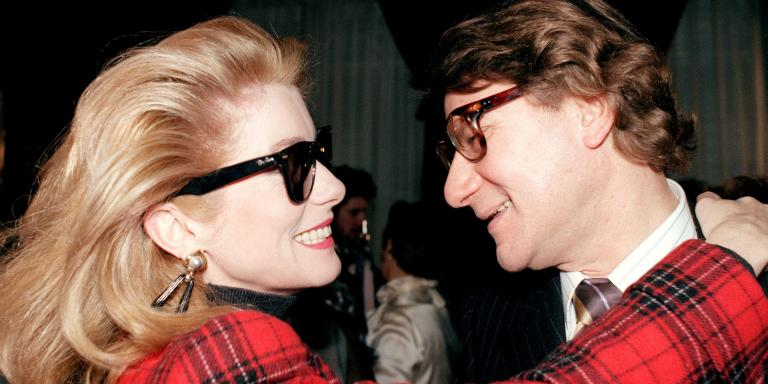 Actress Catherine Deneuve (G) congratulates fashion designer Yves Saint Laurent on January 28, 1987, at the end of the parade of his couture-couture spring-summer 1987 collection. (Photo by PIERRE GUILLAUD / AFP)