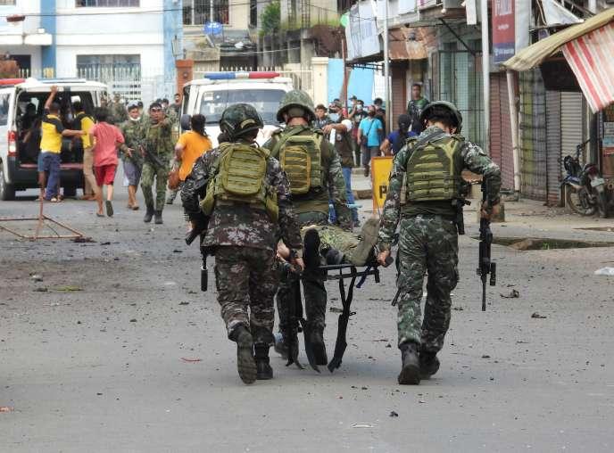 Des soldats transportent l'un des leurs après l'explosion d'une bombe artisanale à Jolo, aux Philippines, lundi 24août.