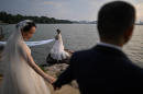 This photo taken on August 5, 2020 shows couples posing for wedding photographers next to East Lake in Wuhan in China's central Hubei province. The city's convalescence since a 76-day quarantine was lifted in April has brought life and gridlocked traffic back onto its streets, even as residents struggle to find their feet again. Long lines of customers now stretch outside breakfast stands, a far cry from the terrified crowds who queued at city hospitals in the first weeks after a city-wide lockdown was imposed in late January to curb the spread of the COVID-19 coronavirus. / AFP / Hector RETAMAL