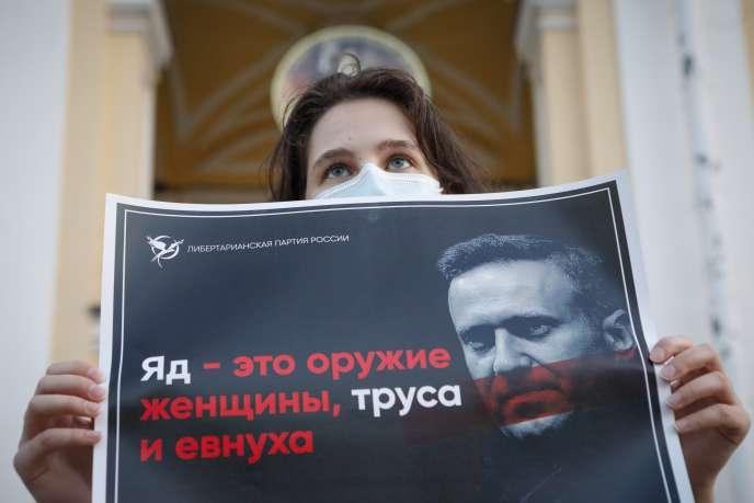 Jeudi 20 août, une manifestante tient une affiche sur laquelle on peut lire «Le poison est l'arme d'une femme, d'un lâche et d'un eunuque» lors d'un piquet de soutien au leader de l'opposition russe, Alexeï Navalny, dans le centre de Saint-Pétersbourg, en Russie.