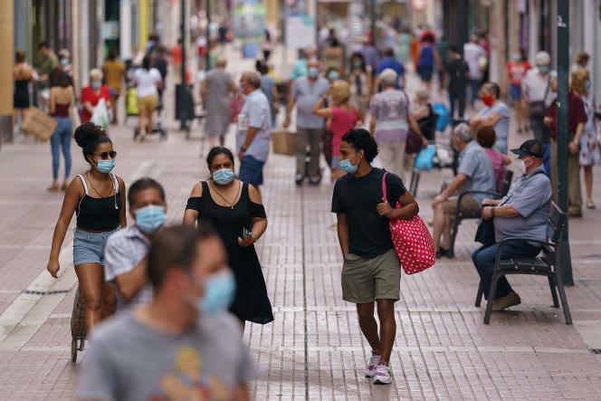Des personnes portant des masques marchent dans une rue commerçante du quartier Las Delicias de Saragosse, dans le nord-est de l'Espagne, le 10 août.