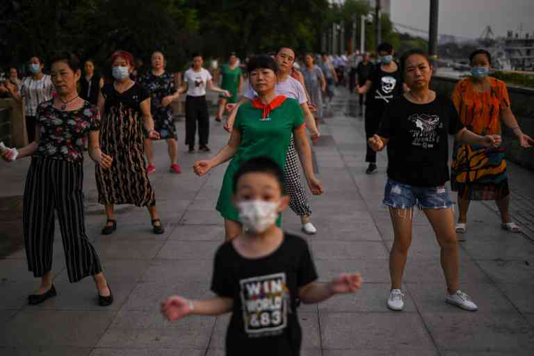 TOPSHOT - This photo taken on August 4, 2020 shows people dancing during the afternoon next to the Yangtze River in Wuhan in China's central Hubei province. The city's convalescence since a 76-day quarantine was lifted in April has brought life and gridlocked traffic back onto its streets, even as residents struggle to find their feet again. Long lines of customers now stretch outside breakfast stands, a far cry from the terrified crowds who queued at city hospitals in the first weeks after a city-wide lockdown was imposed in late January to curb the spread of the COVID-19 coronavirus. / AFP / Hector RETAMAL