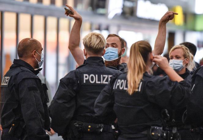 Des forces de l'ordre se préparent à faire des contrôles dans la gare d'Essen, en Allemagne, le 24août. Une amende de 150euros est prévue pour les passagers ne portant pas le masque.