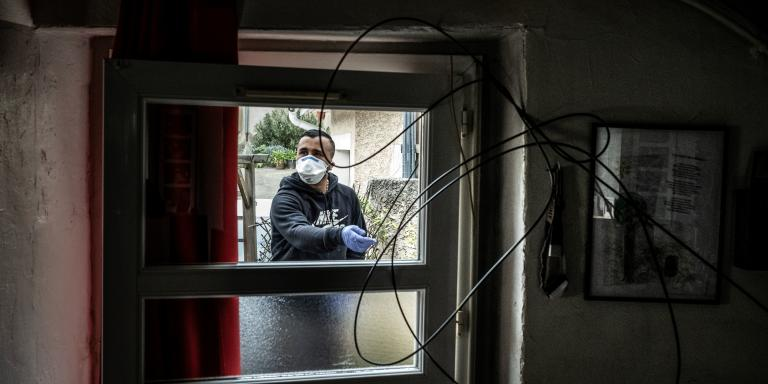 A technician from an internet provider wearing a face mask installs optical fiber in a private home on April 27, 2020 in Givors near Lyon, as the country is under lockdown to stop the spread of the Covid-19 pandemic caused by the novel coronavirus. (Photo by JEAN-PHILIPPE KSIAZEK / AFP)