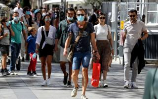 People wearing face masks walk on the Champs Elysees Avenue in Paris, on August 27, 2020. France's prime minister announced on August 27, 2020, that face masks become compulsory throughout Paris and inner suburbs as he detailed a national trend of expanding coronavirus infections. / AFP / Ludovic MARIN