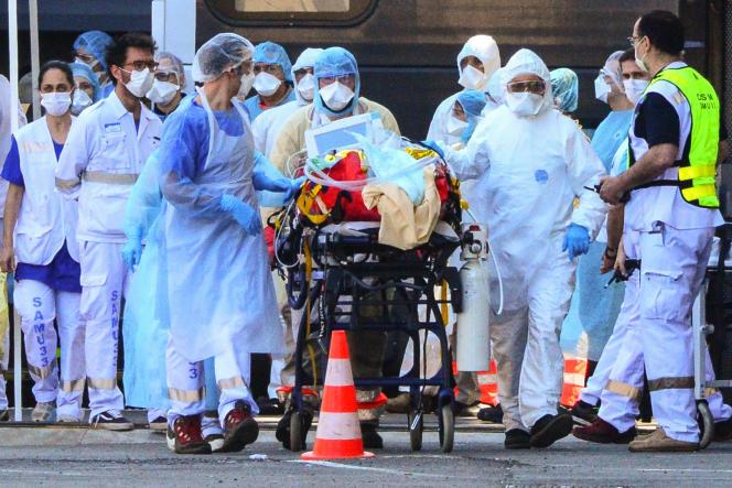 Des aide-soignants transfèrent un patient pour désengorger des services de réanimation surchargés, le 10 avril à la gare de Bordeaux.