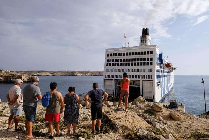 Des touristes, devant un bateau de migrants en quarantaine, le 4 août à Lampedusa (Italie).