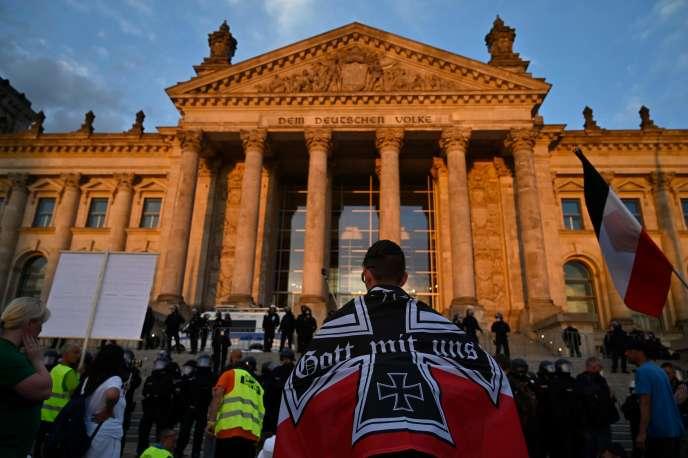 Un manifestant se tient enveloppé dans un drapeau allemand impérial noir-blanc-rouge devant le bâtiment du Reichstag gardé par des policiers à la fin d'une manifestation d'opposants aux mesures mises en place contre la pandémie de Covid-19, à Berlin, le 29 août.