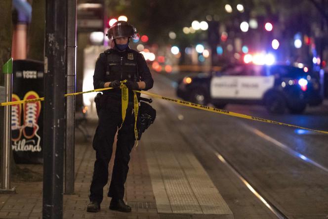 Un policier de Portland attache une ligne de sécurité autour de la scène où a éclaté une fusillade mortelle, non loin d'un rassemblement pro-Trump, le 29 août 2020, à Portland, dans l'Oregon.