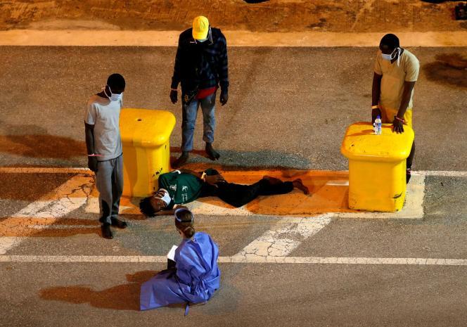 Un employé duHaut-Commissariat aux réfugiés (HCR) s'entretient avec des migrants débarqués dans le port de LaVallette, le 3 août, à Malte.
