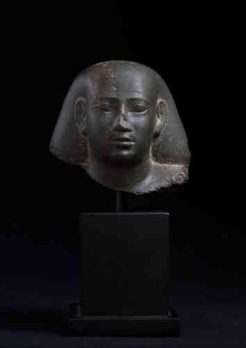 Tête de statue de particulier coiffée d'une perruque à bourse. Egypte, époque saïte, (664-525 av. J.-C.). Provenance : ancienne collection Lord Mac Alpine de West Green, acquis à Braham en 1982.