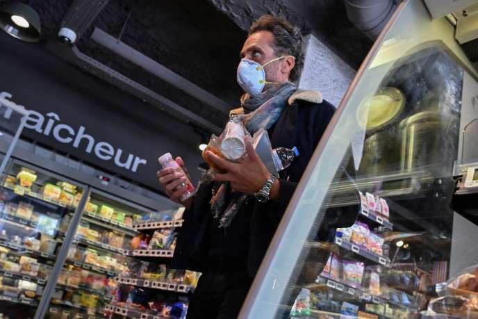 Un client masqué dans un supermarché, à Lyon, le 16 mars 2020.