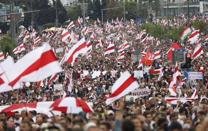 Des manifestants dans les rues de la capitale biélorusse, Minsk, dimanche 6septembre, avec des drapeaux rouge et blanc, l'ancienne version du drapeau officiel devenue signe de protestation contre AlexandreLoukachenko.