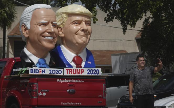 Un passant fait un selfie devant des sculptures en mousse à l'effigie de Donald Trump et de Joe Biden, à Fort Lauderdale (Floride), le 3 septembre.