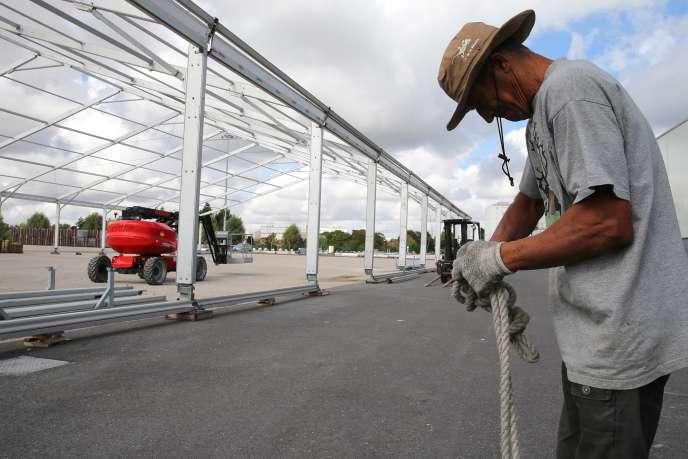 Un ouvrier démonte un chapiteau à Châlons-en-Champagne (Marne), le 17 août, après l'annonce de l'annulation de la foire agricole en raison de la crise sanitaire liée au Covid-19.