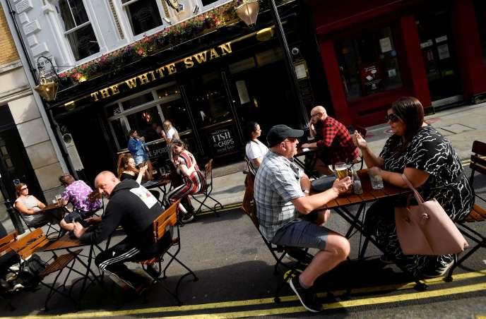 Des personnes buvant un verre en terrasse dans un pub de Covent Gardent, à Londres, le 2 août.