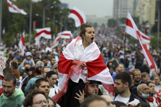 Une jeune femme couverte de l'ancien drapeau biélorusse en signe d'opposition à la réélection d'Alexandre Loukachenko, lors d'une manifestation à Minsk, le 6 septembre 2020.