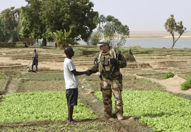 Un soldat de l'opération « Barkhane» visite un agriculteur qui a bénéficié de l'installation d'un réseau d'irrigation par l'armée française à Gao, au bord du fleuve Niger, dans le nord du Mali en mai 2015.