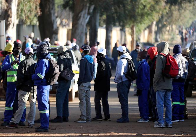 Des demandeurs d'emploi attendent devant un chantier de construction avec l'espoir d'être embauchés, à Eikenhof, au sud de Johannesburg, le 23 juin 2020.