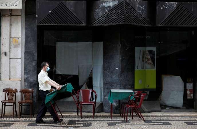 Un serveur installe des tables et des chaises dans la rue, en pleine épidémie de Covid-19, à Lisbonne, au Portugal, le 10septembre2020.