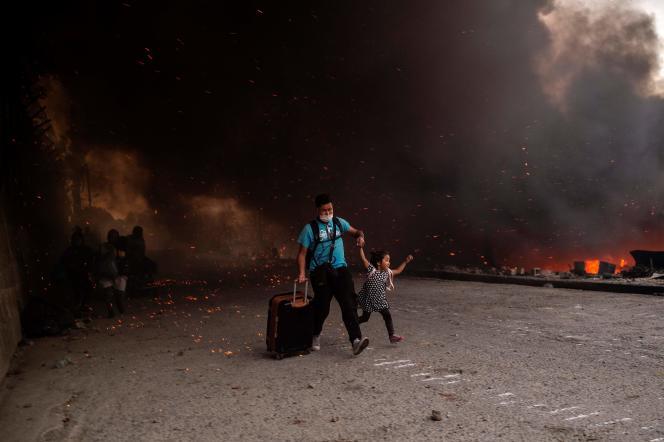 Un migrant et une enfant quittent le camp sur l'île de Lesbos (Grèce), le 9 septembre.