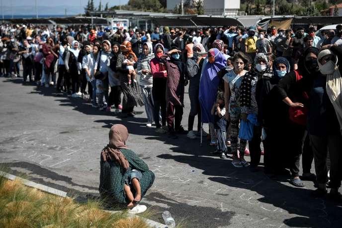 Des réfugiés, devenus sans abri après l'incendie qui a dévasté un camp sur l'île grecque de Lesbos, lors d'une distribution d'eau et de nourriture sur le parking d'un supermarché, le 10 septembre 2020.