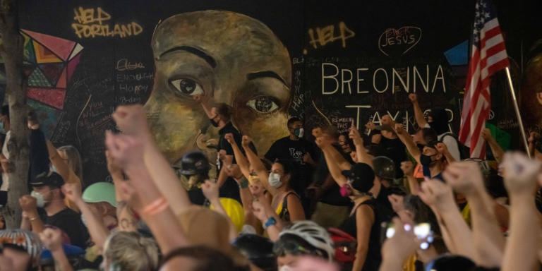 """Black Lives Matter demonstrators, including members of the """"Mom Wall"""" group, dressed in yellow, raise their fists during a moment of silence in front of a mural of Breonna Taylor, a black woman who was killed by police. *** Local Caption *** activism Black Lives Matter BLM city conflict crowd crowds demonstrating demonstration demonstrator demonstrators Federal Moms Mom Wall mural OR Portland portrait protest protester protesters protesting rally urban USA"""