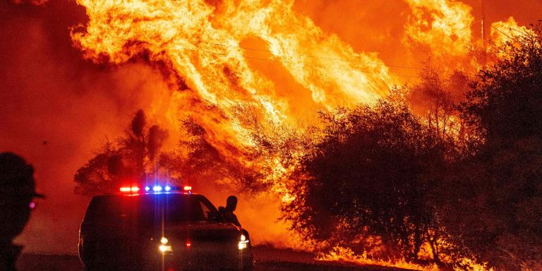 A law enforcement officer watches flames launch into the air as fire continues to spread during the Bear fire in Oroville, California on September 9, 2020.     Dangerous dry winds whipped up California's record-breaking wildfires and ignited new blazes, as hundreds were evacuated by helicopter and tens of thousands were plunged into darkness by power outages across the western United States. / AFP / JOSH EDELSON