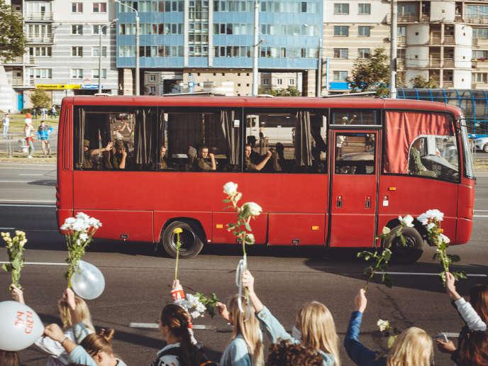 A Minsk, le 13,août, des militaires en bus adressent un signe de victoire aux femmes, qui ont formé une chaîne de solidarité.
