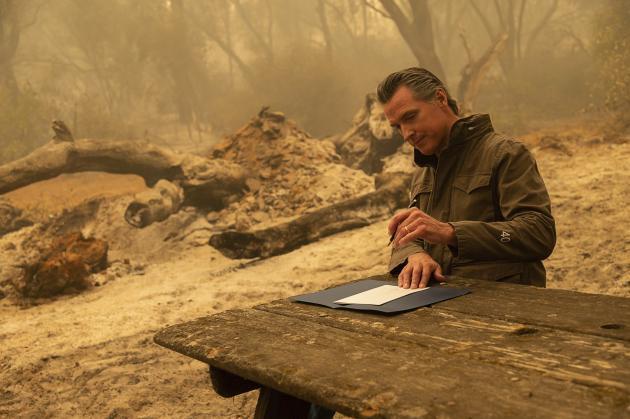 Le gouverneur Gavin Newsom signe un projet de loi après avoir visité la zone incendiée près d'Oroville, comté de Butte, Californie, le 11 septembre.