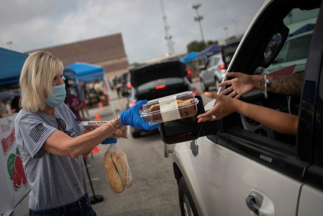 Une bénévole donne du pain et des pâtisseries aux habitants de San Antonio, Texas, affectés par la crise économique du Covid-19, le 17 juillet.