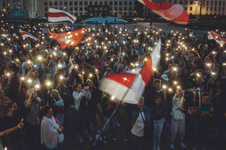 People are shining flashlights of their cell phones and singing at the Independence square. August 21, 2020, Minsk, Belarus.