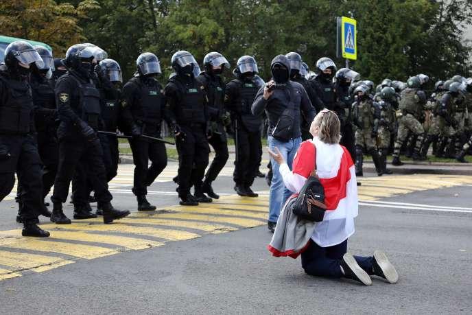 Une manifestante biélorusse s'agenouille devant les forces de l'ordre, à Minsk, dimanche 13 septembre.