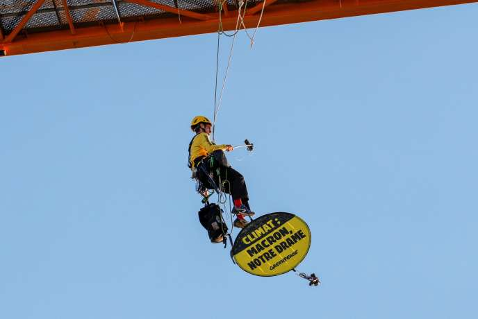 Un activiste de Greenpeace tient une bannière «Climat : Macron, notre drame» sur le chantier de la cathédrale Notre-Dame, le 9 juillet à Paris.