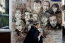 A woman walks past a painting by French street artist and painter Christian Guemy, known as C215, in tribute to members of Charlie Hebdo newspaper who were killed by jihadist gunmen in January 2015, in Paris, on August 31, 2020. - Fourteen alleged accomplices in the 2015 jihadist attacks on the Charlie Hebdo satirical weekly, on a kosher supermarket and in the southern Paris suburb Montrouge go on trial on September 2, more than half-a-decade after days of bloodshed that still shock France. The attacks heralded a wave of Islamist violence that has left 258 people dead and raised unsettling questions about modern France's ability to preserve security and harmony for a multicultural society. (Photo by THOMAS COEX / AFP) / RESTRICTED TO EDITORIAL USE - MANDATORY MENTION OF THE ARTIST UPON PUBLICATION - TO ILLUSTRATE THE EVENT AS SPECIFIED IN THE CAPTION