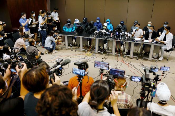 Les proches des douze militants détenus par Pékin s'expriment masqués,le 12 septembre à Hongkong.