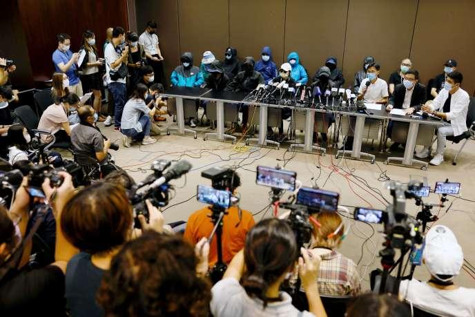 Des proches des douze militants détenus par Pékin s'expriment masqués le 12 septembre à Hong Kong.