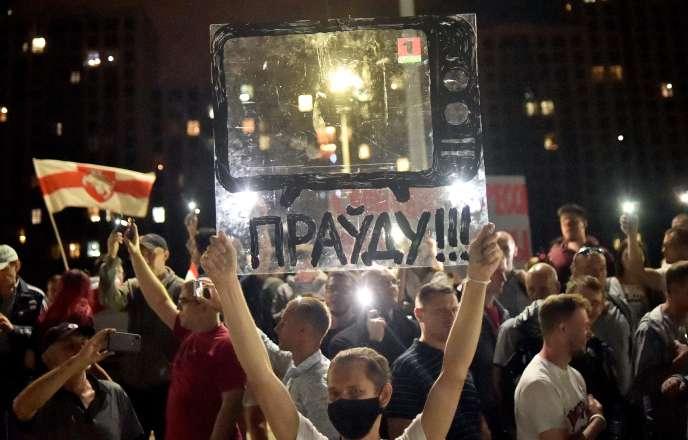 Un manifestant brandit l'image transparente d'un poste de télévision, portant le message« La vérité !!!», lors d'une protestation contre les violences policières se déroulant devant le siège de la télévision étatique, le 15 août à Minsk.