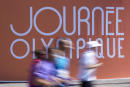 "This picture taken on June 23, 2019 shows people running in front of a sign reading ""Journee Olympique"" (""Olympic day"") as they take part in the ""Journee Olympique"" (""Olympic day"") in Paris. - A total of thirty Olympic and paralympic sports will be presented on Place de la Concorde in Paris on June 23, 2019. (Photo by Kenzo TRIBOUILLARD / AFP)"