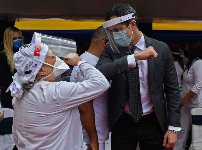 TOPSHOT - Venezuelan opposition leader Juan Guaido (R), wearing a face mask and shield, greets a supporter during a tribute to health workers who died from COVID-19, at the Venezuelan Medical Federation in Caracas, on September 10, 2020. / AFP / Federico PARRA