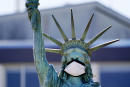 FILE - In this Aug. 26, 2020, file photo, the face on a replica of the Statue of Liberty covers with a protective face mask against the coronavirus. The 1/18th scale replica on Seattle's Alki Beach was erected in 1952 and recast in 2006. (AP Photo/Elaine Thompson)