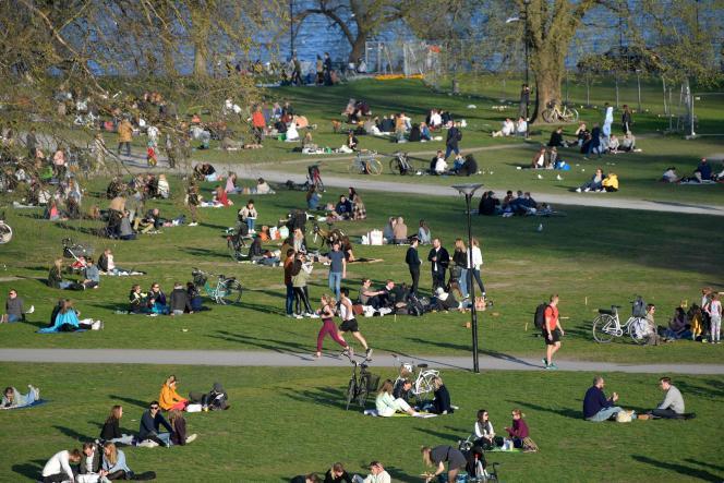 Des gens profitent du temps printanier, dans un parc de Stockholm, le 22 avril.