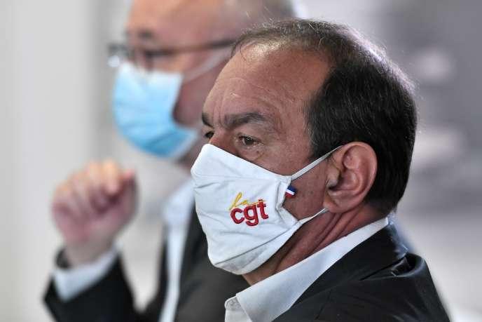 Philippe Martinez, le secrétaire général de la CGT, écoute le premier ministre lors de sa visite dans une usine Bic, à Montévrain,le 14 septembre.